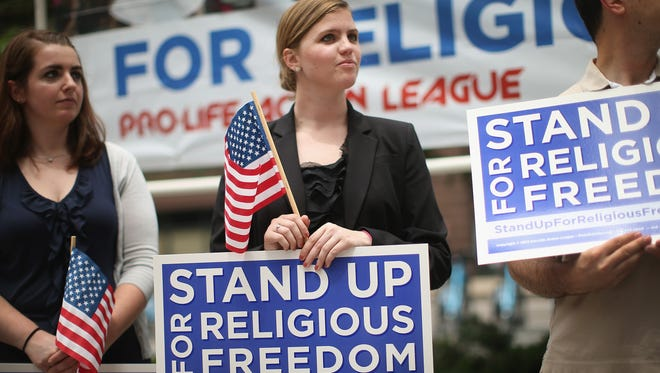 Religious freedom advocates hold a rally in Chicago to support the Supreme Court's decision in the Hobby Lobby case Monday.