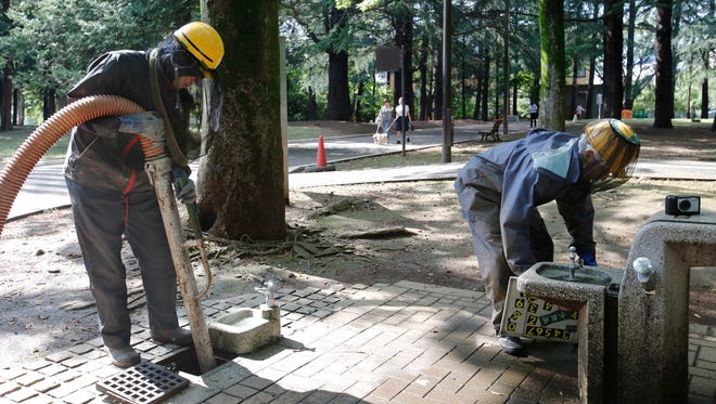 Workers clean the drain at Yoyogi Park in Tokyo, Tuesday, Sept. 2, 2014.
