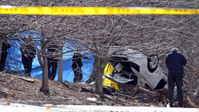 Investigators work at the scene of a fatal car accident on Gate Hill Road in Stony Point April 9, 2014.