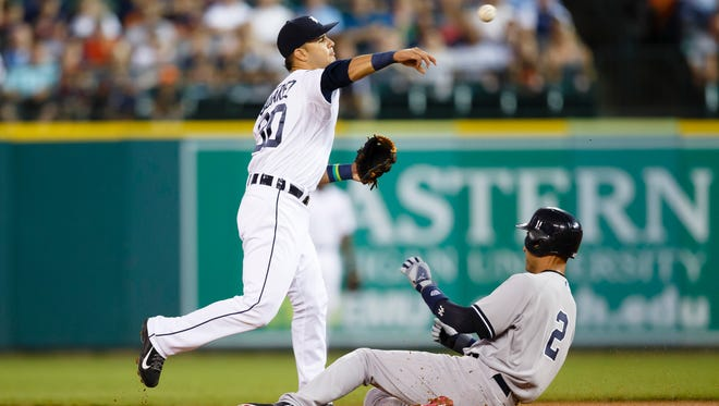 Detroit Tigers shortstop Eugenio Suarez (30) makes a throw to first to complete a double play as Yankees shortstop Derek Jeter (2) slides into second first inning at Comerica Park on Tuesday.