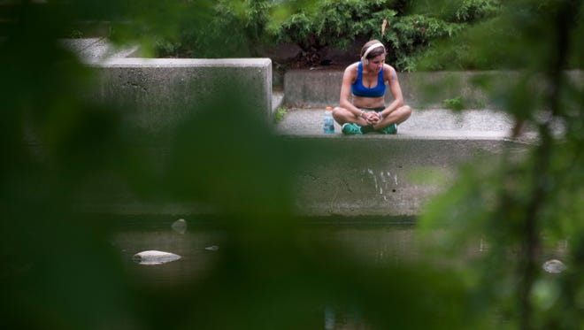 A young woman takes a break from her workout by the Red Cedar River on Thursday, July 21, 2016 near Wells Hall at Michigan State University in East Lansing. Temperatures reached into the 90s. The National Weather Service in Grand Rapids issued a heat advisory, effective from 1 p.m. Thursday to 7 p.m. Friday.