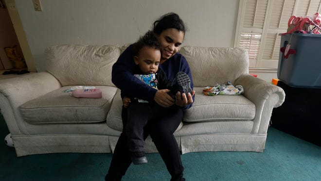 Shannon Henderson, gets her son, Justin, 1, dressed before leaving home for her job as a part-time customer service representative at Wal-Mart in Sacramento, Calif. Henderson is one of an estimated 40 million American workers for who calling in sick is a luxury. If they don't work, they don't get paid.