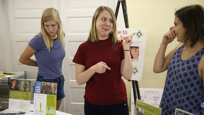 Kira Sullivan, center, who has a rare condition of aplastic anemia, chats with friends at the First Presbyterian Church Sunday where the youth group is planning a bone marrow registry Saturday to raise awareness and get donors for the bone marrow transplant that she will need.
