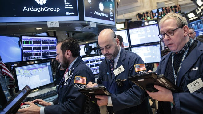 Wall Street reacted in an upbeat mood after the Fed raised rates Wednesday afternoon. Traders work on the floor of the New York Stock Exchange,