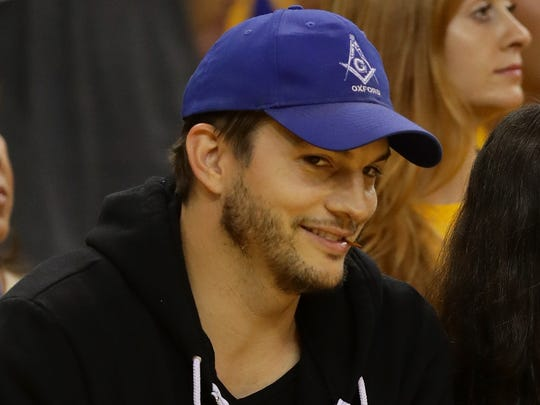 A ball cap-wearing Ashton Kutcher and Mila Kunis are shown at a basketball game on June 5, 2016, in Oakland, Calif.