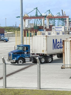 Tractor drivers maneuver their containers inside the expanded container yard at the Port Authority of Guam on Cabras Island on Wednesday, Dec. 9, 2015.