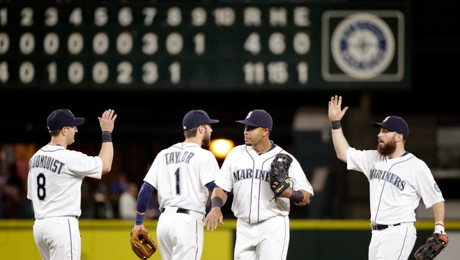 Seattle Mariners' Willie Bloomquist (8), Chris Taylor (1), Nelson Cruz and Dustin Ackley share congratulations after the team beat the San Diego Padres in a baseball game Tuesday, May 12, 2015, in Seattle. The Mariners won 11-4.