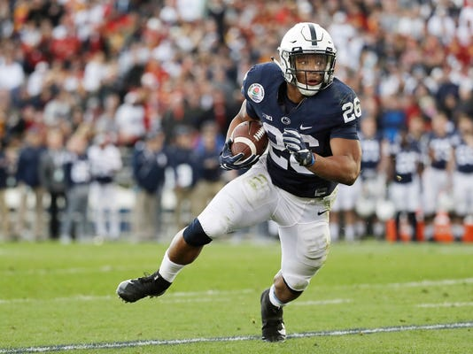 File-This Jan. 2, 2017, file photo shows Penn State Nittany Lions running back Saquon Barkley looking for room to run against USC during the first half of the Rose Bowl NCAA college football game,  in Pasadena, Calif. Southern California quarterback Sam Darnold and Barkley put on a show at the Rose Bowl to end last season, and established themselves as two of the biggest stars in college football coming into 2017. Now the two Heisman Trophy contenders highlight The Associated Press preseason All-America team released Tuesday.  (AP Photo/Doug Benc, File)
