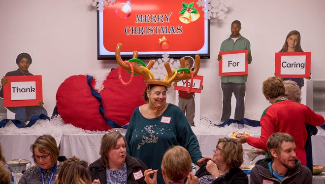 Debby Gamache, staff advocate for CASA, center, takes the morning off from her 60-80 kid case load to celebrate Christmas at the organization's annual party Friday morning.