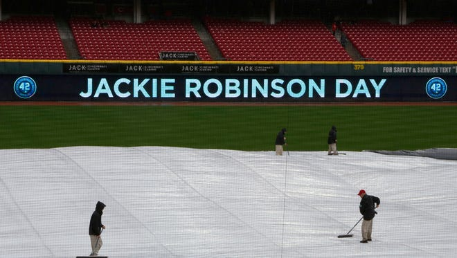 Members of the Great American Ball Park ground crew sweep water off the tarp before a game between the Cardinals and Reds.