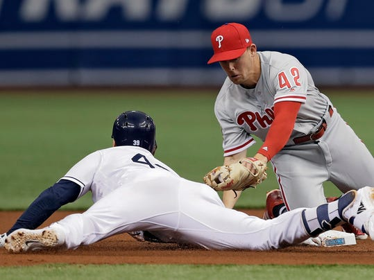 Tampa Bay Rays' Kevin Kiermaier, left, slides around a tag by Philadelphia Phillies second baseman Scott Kingery after hitting a single and taking second during the first inning of a baseball game Sunday, April 15, 2018, in St. Petersburg, Fla. Kiermaier injured his hand on the play and left the game at the end of the inning. (AP Photo/Chris O'Meara)