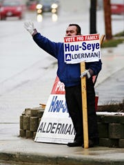 Aldermanic incumbent Job Hou-Seye waves to passing motorists at 14th and Erie on a rainy election day Tuesday April 4, 2017 in Sheboygan, Wis.