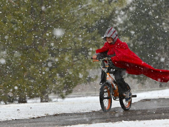 Six-year-old Isaiah Frey's blanket turns into a cape as he rides his bicycle in a snowstorm at Gibson Park Monday afternoon.