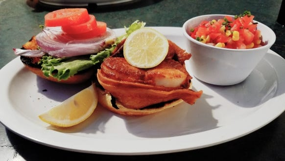 Crabby's scallop burger is served on a slightly over toasted bun with three large sweet scallops wrapped by two pieces of salty, crispy bacon.