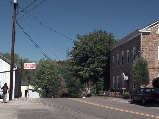 Text: 1999.0930.09.3-DIGITAL IMAGE-CAMPSPRINGS-OVERALL-The historic Four-Mile House, built in 1864 and listed on the National Historic Register is across the street from Reitman Auto Parts in Camp Springs, Campbell County. (if we need an ID the man walking