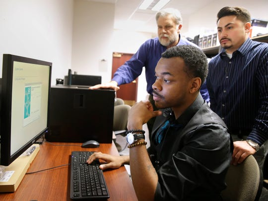 Avery White learns to program computers at Twin Disc Corp. under a new jobs training program in Racine called Start IT. Twin Disc supervisor Joshua Sosa (right) helps White. Also watching is Cory Mason, chief information officer at Twin Disc who helped set up the program, meant for young people seeking family supporting IT jobs.