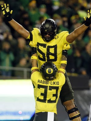 Oregon running back Cyrus Habibi-Likio hoists left tackle Penei Sewell after Habibi-Likio scored a touchdown against Arizona last season at Autzen Stadium. [Andy Nelson/The Register-Guard] - registerguard.com