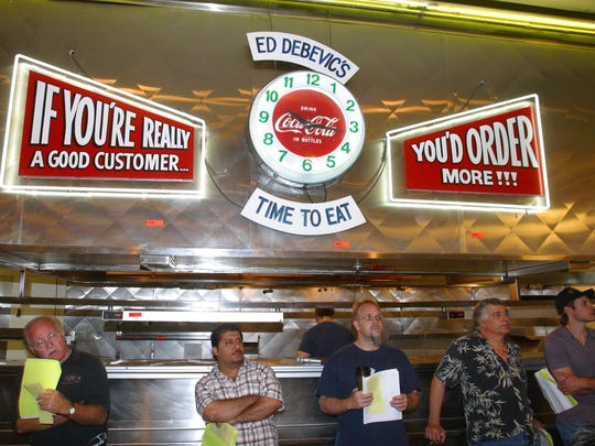 Bidders lean against the counter at Ed Debevic's in