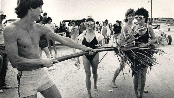 """Curtis Ortez of San Antonio salutes fellow beachgoers with the """"national flag of Port Aransas during spring break on March 17, 1985. Left to right are Mari Rampy, Dawn Faglie and Angie Garrett, all of Austin."""