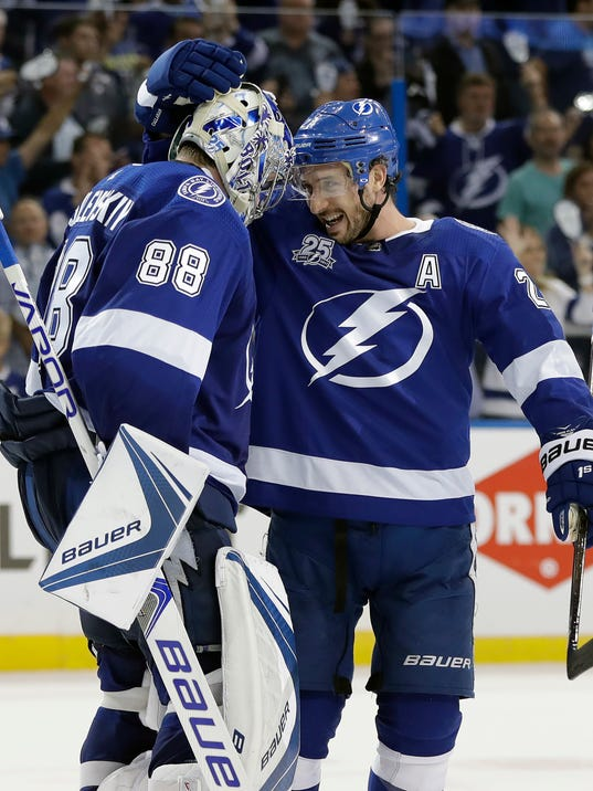 Tampa Bay Lightning goaltender Andrei Vasilevskiy (88) celebrates with Ryan Callahan (24) after the Lightning defeated the New Jersey Devils 5-2 during Game 1 of an NHL first-round hockey playoff series Thursday, April 12, 2018, in Tampa, Fla. (AP Photo/Chris O'Meara)
