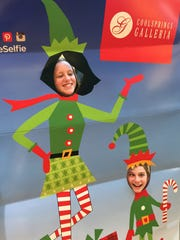 Katie Smith and Laken McClain pose in a Elf cutout at Cool Springs Galleria during Black Friday on Friday Nov. 28, 2014.