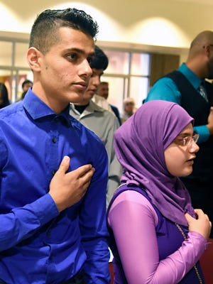 Brother and sister Yousif, left, and Ghadeer Mustafa hold their hands over their hearts as they say the Pledge of Allegiance after taking the Oath of Allegiance to become citizens of the United States during a ceremony at the Loma Colorado Library, Friday, Aug. 19, 2016 in Rio Rancho, N.M.