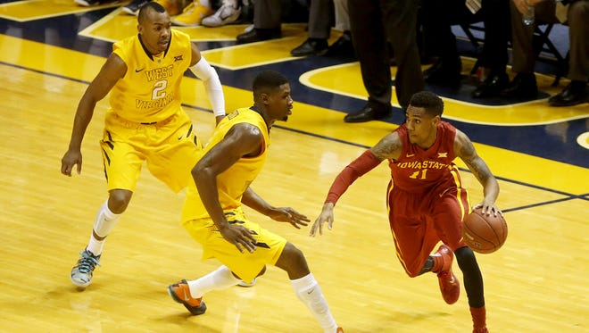 Iowa State Cyclones guard Monte Morris (11) handles the ball as West Virginia Mountaineers guard Jevon Carter (2) and forward Jonathan Holton (1) defend during the first half at the WVU Coliseum.