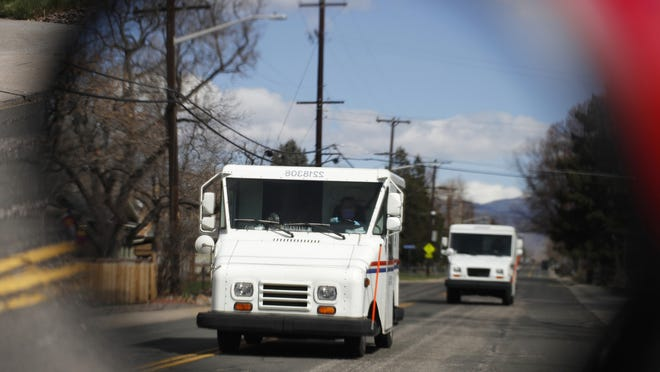 In this March 31 file photo, United States Post Office delivery trucks are reflected in the side mirror of a vehicle as postal delivers set off on their daily rounds in Arvada, Colo.