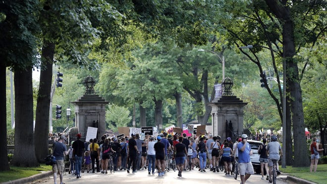 Protesters walk through the gate of a private street not far from the home of Mark and Patricia McCloskey on July 3, 2020, in St. Louis.