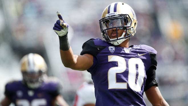 Washington Huskies defensive back Kevin King points to the stands after making a tackle for a loss against Rutgers.