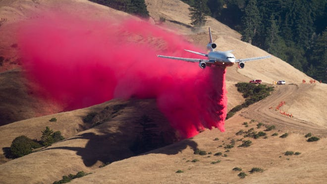 TOPSHOT - A plane drops fire retardant while battling the Soberane Fire in Carmel Highlands, California on July 23, 2016.  The fire has scored more than 10,000 acres and threatens 1,650 structures according to Cal Fire.   / AFP PHOTO / NOAH BERGERNOAH BERGER/AFP/Getty Images ORIG FILE ID: AFP_DJ2PU