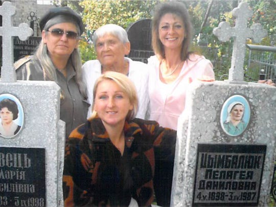 Nina Grigg (Zimbalyk) with her daughters at the grave sites of her mother and grandmother.