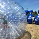 """Teams compete in """"Roller Dash,"""" a Hungry Hungry Hippo-like game July 23, 2016 during the Labatt Undomesticated Games on Belle Isle."""