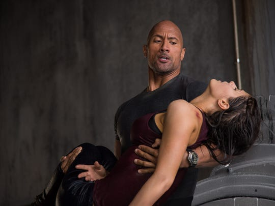 "Dwayne Johnson carries Alexandra Daddario in ""San Andreas."""