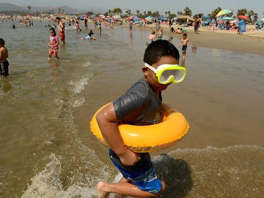 Francisco Macias Jr. plays in the water near Ventura