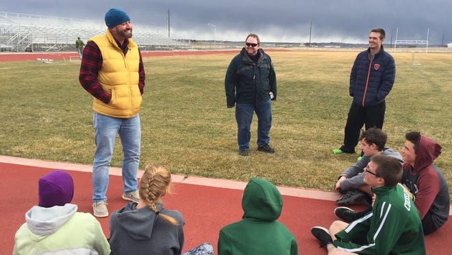 Heritage Christian Academy High School track coach Joe Packard, far left, talks to his team before a workout at Severance Middle School on Thursday.
