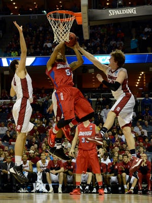 Dayton Flyers forward Devin Oliver (5) drives to the basket against Stanford Cardinal guard Robbie Lemons (right) and center Stefan Nastic (4) during the first half of the semifinals in the south regional of the 2014 NCAA Mens Basketball Championship tournament at FedExForum.