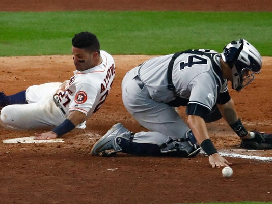Houston Astros' Jose Altuve scores the game-winning run past New York Yankees catcher Gary Sanchez during the ninth inning of Game 2 of baseball's American League Championship Series Saturday, Oct. 14, 2017, in Houston. The Astros won 2-1 to take a 2-0 lead in the series. (AP Photo/Eric Gay)