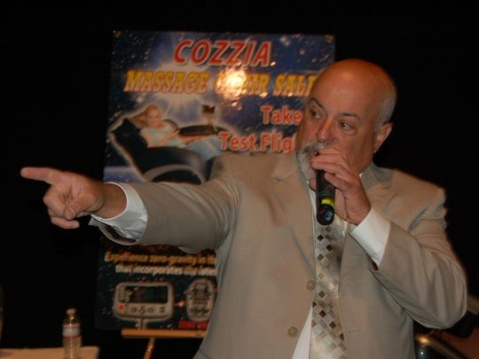 An auctioneer takes a bid from an audience member during