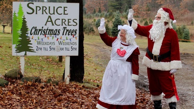 Santa and Mrs. Claus wave to those driving by Spruce Acres during a Kiwanis Club service project Saturday.