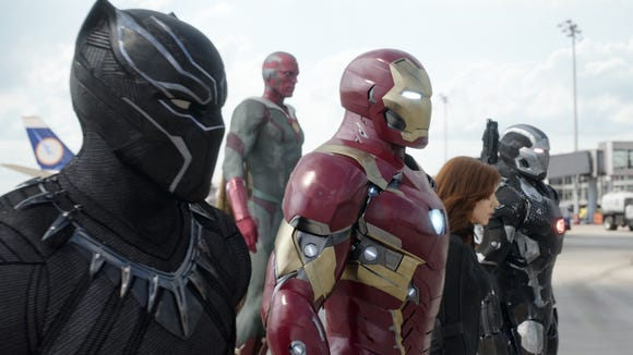 """This image released by Disney shows, from left, Chadwick Boseman as Panther, Paul Bettany as Vision, Robert Downey Jr. as Iron Man, Scarlett Johansson as Natasha Romanoff, and Don Cheadle as War Machine in a scene from """"Marvel's Captain America: Civil War."""""""