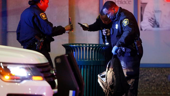 Police search a trashcan and backpack at the scene of a stabbing Downtown Monday. The female victim is expected to survive.