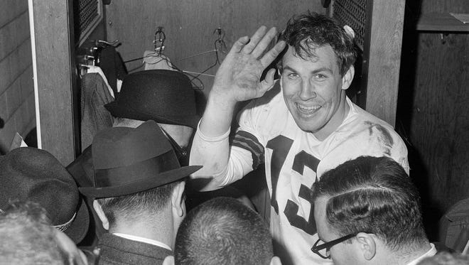 FILE- In this Dec. 27, 1964, file photo, Cleveland Browns quarterback Frank Ryan salutes in dressing room as he talks with reporters after they defeated the Indianapolis Colts 27-0 in the NFL championship football game in Cleveland, Ohio. Saturday marks 50 years since the Browns won the NFL title, the last championship for this city's three pro sports franchises. For fans, it's been mostly misery since. That's why LeBron James' return provides something dearly needed: hope.  (AP Photo/File)