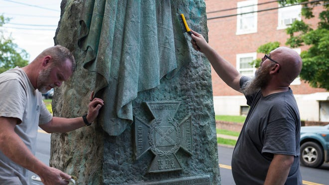 At left Norman Holliman of Maryville and Phillip Cook of Powell scrub paint off a defaced Confederate monument in Fort Sanders Thursday, Aug. 17, 2017.