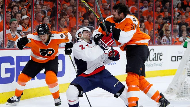 The Flyers' Colin McDonald, right, and Waashington's Matt Niskanen, center, collide as Ryan White skates past during the second period of Game 4.
