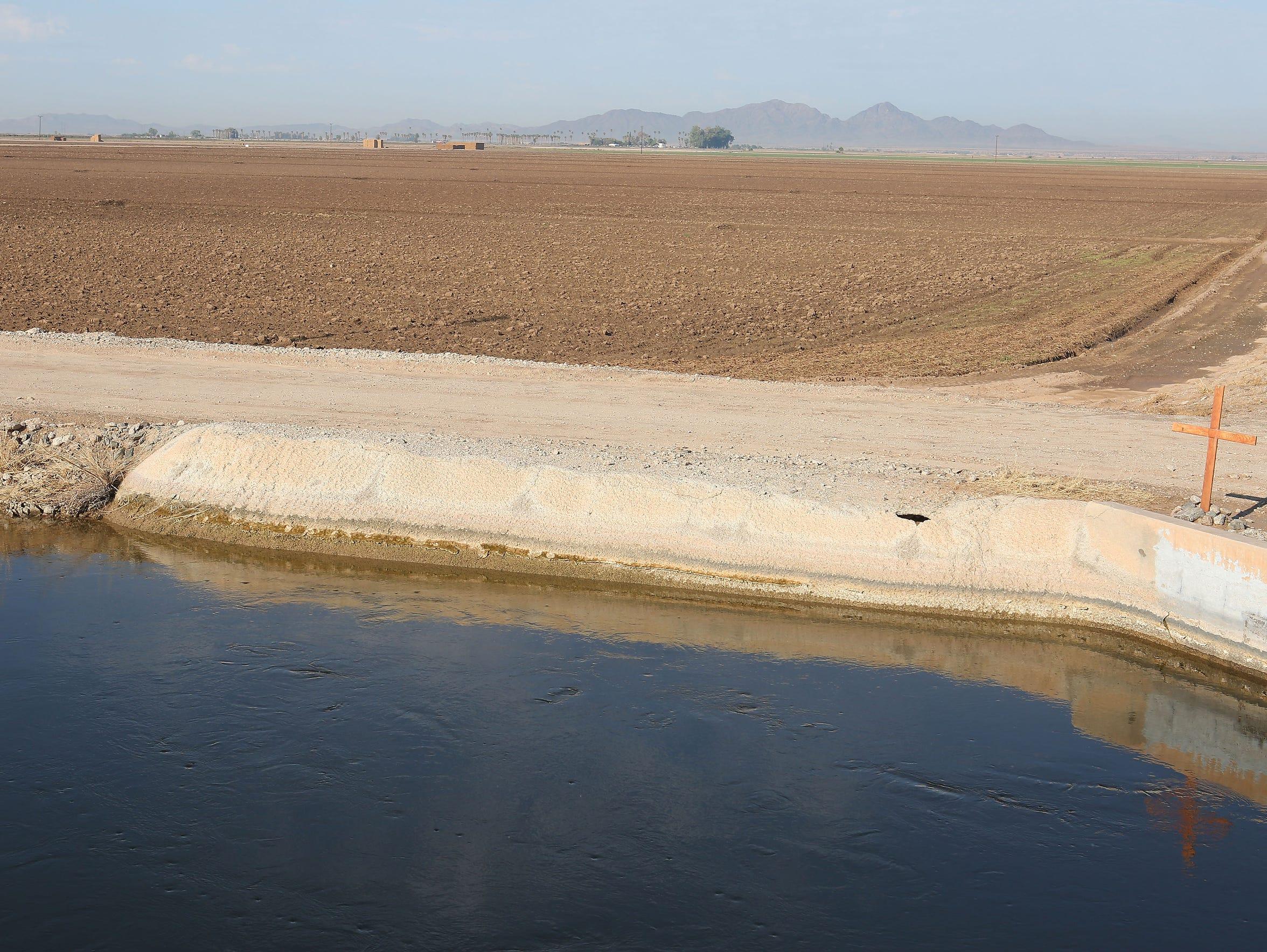 A dry field runs alongside an irrigation canal near