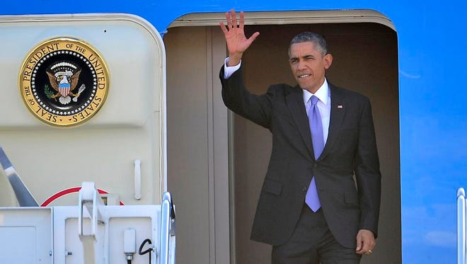 President Obama waves as he arrives at Berry Field.
