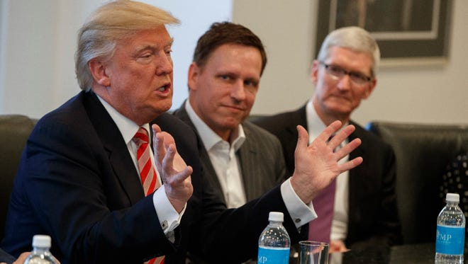 Apple CEO Tim Cook, right, and PayPal founder Peter Thiel, center, listen as President-elect Donald Trump speaks during a meeting with technology industry leaders at Trump Tower in New York, Wednesday, Dec. 14, 2016. Cook is among tech CEOs urging Trump to keep the U.S. in the Paris climate accord.