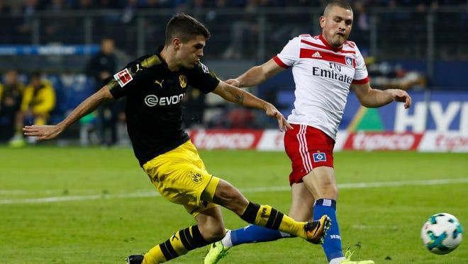 Christian Pulisic scores Borussia Dortmund's third goal in a 3-0 win over Hamburg in Hamburg.
