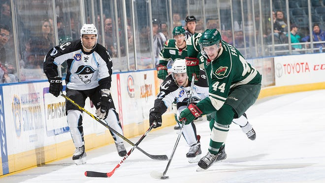 Iowa defenseman Justin Falk carries the puck away from Milwaukee's Joe Pendenza in the first period Wednesday night in the Wild's 3-2 win.
